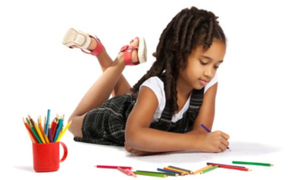 cheerful girl draws pencil lying on the floor